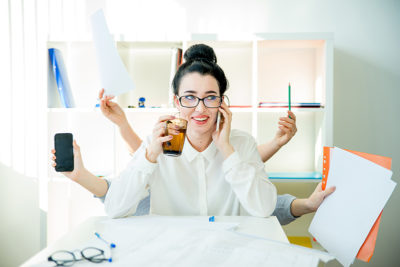 A successful businesswoman is multitasking in office
