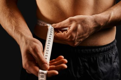 Sportsman measuring waist with centimeter tape